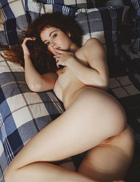 Redhead stunner, Adel C, lays seductively in bed and showing off her goods