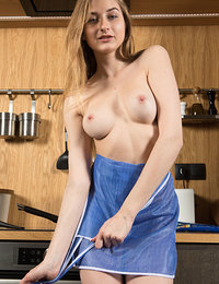 Amelia Gin displays her sexy apron as she poses in the kitchen.