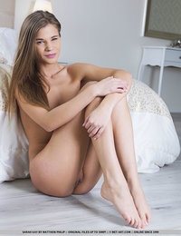 Sarah Kay sensually strips on the bed baring her sexy