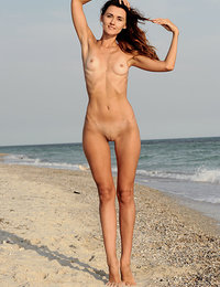 Lorian playfully poses by the beach as she bares her slender