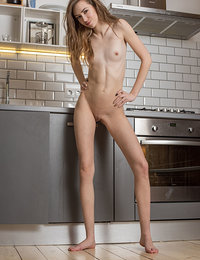 Madison strips on the kitchen counter top baring her delectable pussy.