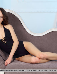 Debora A displays her tight, nubile body as she strips on the couch.