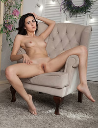 Mona bares her slender body with pink nipples and small pussy on the chair.
