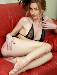 Janelle B flaunts her sexy lingerie as she poses on the couch.